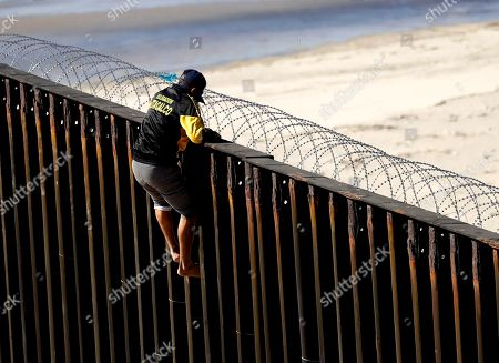 A man tries to get over a border structure topped with concertina wire, in Tijuana, Mexico. Migrants in a caravan of Central Americans scrambled to reach the U.S. border, catching rides on buses and trucks for hundreds of miles in the last leg of their journey Wednesday as the first sizable groups began arriving in the border city of Tijuana