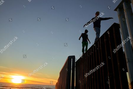Two Central American migrants walk along the top of the border structure separating Mexico and the United States, in Tijuana, Mexico. Migrants in a caravan of Central Americans scrambled to reach the U.S. border, catching rides on buses and trucks for hundreds of miles in the last leg of their journey Wednesday as the first sizable groups began arriving in the border city of Tijuana