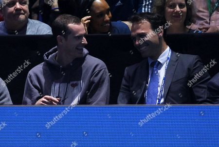 Andy Murray of Great Britain watches the action court side with Ross Hutchins, laughing