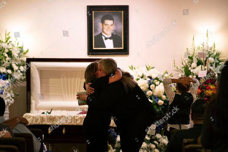 Stock Image of Cheryl Tate, center right, mother Cody Coffman, is comforted by a mourner as her son, Chayse, looks at the coffin at a funeral service for Coffman, in Camarillo, Calif. The 22-year-old was among a dozen people killed in a Nov. 7 shooting at a country music bar in Thousand Oaks, Calif