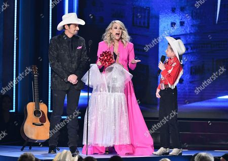 Carrie Underwood, center, holds a bubble wrap dress given to her by Brad Paisley, left, as Mason Ramsey, right, looks on