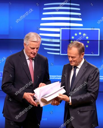 Stock Picture of EU chief Brexit negotiator Michel Barnier, left, and European Council President Donald Tusk flip through the pages of a draft withdrawal agreement prior to a media conference at the Europa building in Brussels on . In a hard-won victory on Wednesday, British Prime Minister Theresa May persuaded her fractious Cabinet to back a draft divorce agreement with the European Union