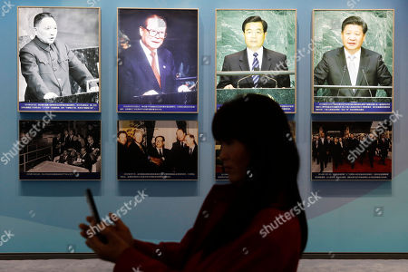 A Chinese visitor takes photo in front of pictures showing former leaders Deng Xiaoping, Jiang Zemin, Hu Jintao and Chinese President Xi Jinping at an exhibition marking the 40th anniversary of China's reform and opening up at the National Museum of China, in Beijing, China, 15 November 2018.