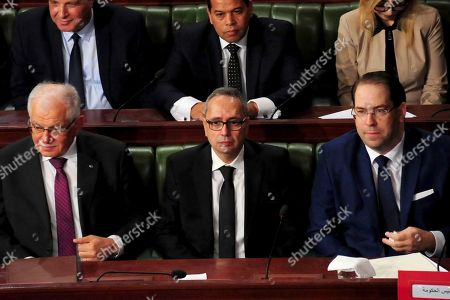This photo dated, shows Tunisia's Premier, Youssef Chahed, right, new justice minister Karim Jamoussi, center, and new public fonction minister Kamel Morjane, who served as defense and foreign minister under the now-toppled Ben Ali, during a confidence vote held at the National Assembly in Tunis, Tunisia