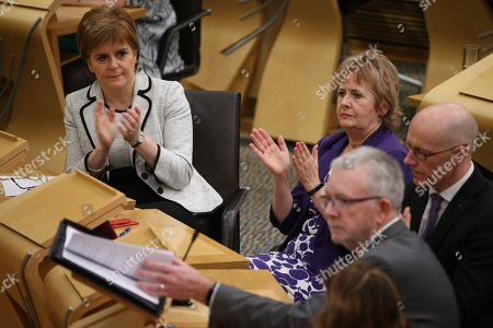 Nicola Sturgeon, First Minister of Scotland and Leader of the Scottish National Party (SNP), Roseanna Cunningham, Cabinet Secretary for Environment, Climate Change and Land Reform, and John Swinney, Deputy First Minister and Cabinet Secretary for Education and Skills, applaud Michael Russell, Cabinet Secretary for Government Business and Constitutional Relations or 'Brexit Minister' after his statement.