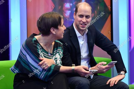 Prince William, (R) listens to Director of BBC Children's Alice Webb (L) as they try out an App designed to combat online bullying during a visit BBC Broadcasting House