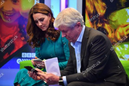 Catherine, Catherine Duchess of Cambridge, (L) sits with Director-General of the BBC Tony Hall (R) as they try out an App designed to combat online bullying during a visit BBC Broadcasting House