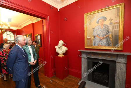 Prince Charles admires a painting of The Queen Mother accompanied by Chairman Fiona Grant during a visit to The Royal Society of Musicians of Great Britain