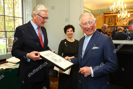 Prince Charles is presented with a gift by architect Russell Taylor during a visit to The Royal Society of Musicians of Great Britain