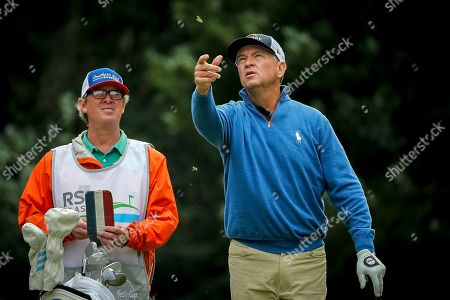 Davis Love III, right, checks the wind on the third tee during the first round of the RSM Classic golf tournament, in St. Simons Island, Ga