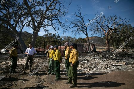 U.S. Secretary of the Interior Ryan Zinke, second from left, talks to firefighters while visiting decimated Paramount Ranch, in Agoura Hills, Calif. The landmark film location burned to the ground by the Woolsey Fire