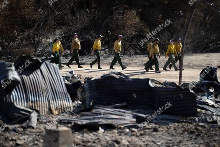 Firefighters walk arrive at decimated Paramount Ranch for a meeting with U.S. Secretary of the Interior Ryan Zinke, in Agoura Hills, Calif. The landmark film location burned to the ground by the Woolsey Fire