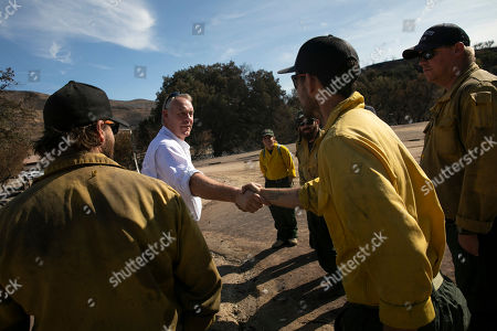 U.S. Secretary of the Interior Ryan Zinke, second from left, shakes hands with firefighters while visiting decimated Paramount Ranch, in Agoura Hills, Calif. The landmark film location burned to the ground by the Woolsey Fire
