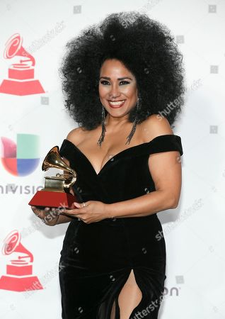 "Aymee Nuviola poses in the press room with the award for best tropical fusion album for ""Como Anillo al Dedo"""