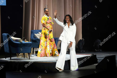 "Tracee Ellis Ross, Michelle Obama. Former first lady Michelle Obama greets the audience as Tracee Ellis Ross watches at the ""Becoming: An Intimate Conversation with Michelle Obama "" event at the Forum, in Inglewood, Calif"