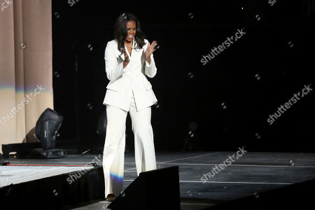 "Former first lady Michelle Obama greets the audience at the ""Becoming: An Intimate Conversation with Michelle Obama "" event at the Forum, in Inglewood, Calif"