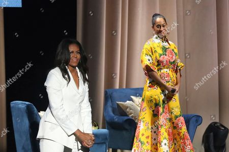 "Tracee Ellis Ross, Michelle Obama. Former first lady Michelle Obama, left, enters the stage after being introduced by Tracee Ellis Ross at the ""Becoming: An Intimate Conversation with Michelle Obama "" event at the Forum, in Inglewood, Calif"