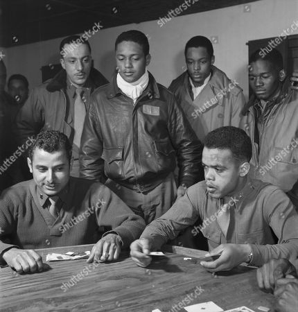 Stock Image of Tuskegee Airmen Playing Cards in Officers' Club, Seated, left to right: Robert Spurlock, Washington, DC; Harold M. Morris, Seattle, WA, Class 44-D. Standing, left to right: Conrad A. Johnson, New York, NY, Class 44-G; Ronald W. Reeves, Washington, DC, Class 44-G; Leroy Roberts, Jr., Toccoa, GA, Class 44-E; Calvin J. Spann, Rutherford, NJ, Class 44-G, Ramitelli, Italy, Toni Frissell, March 1945