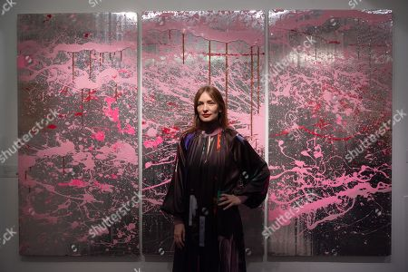 Stock Picture of Serbian fashion designer Roksanda Ilincic poses with artwork titled Cherry Blosson XL (2007) by artist Rob Pruitt