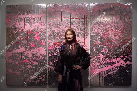 Serbian fashion designer Roksanda Ilincic poses with artwork titled Cherry Blosson XL (2007) by artist Rob Pruitt