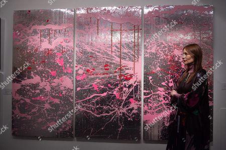 Serbian fashion designer Roksanda Ilincic views with artwork titled Cherry Blosson XL (2007) by artist Rob Pruitt