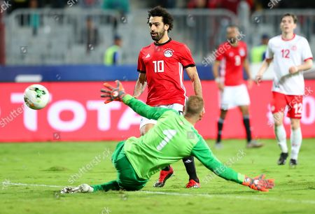Egypt's Mohamed Salah (C) in action against Tunisia's goalkeeper Farouk Ben Mustapha (bottom) during the Africa Cup of Nations (AFCON) 2019 qualifying soccer match between Egypt and Tunisia in Alexandria, Egypt, 16 November 2018.