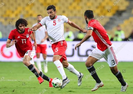 Stock Image of Tunisia's Oussama Haddadi (C) in action against Egyptian players Mohamed Elneny (L) and Ahmed Elmohamady (R) during the Africa Cup of Nations (AFCON) 2019 qualifying soccer match between Egypt and Tunisia in Alexandria, Egypt, 16 November 2018.
