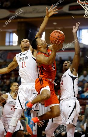 Virginia Tech's Justin Robinson, center, drives between Northeastern's Jeremy Miller, at left, and Shaquille Walters in the first half of an NCAA college basketball game at the Charleston Classic at TD Arena, in Charleston, S.C. Virginia Tech defeated Northeastern 88-60