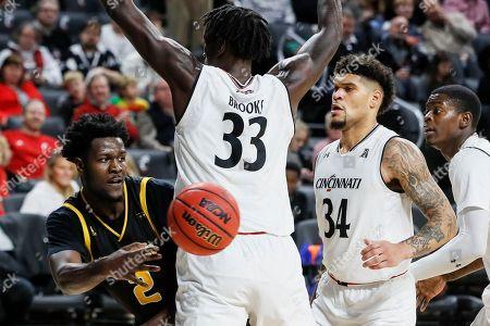 Bobby Arthur-Williams, Nysier Brooks. Milwaukee's Bobby Arthur-Williams (2) passes the ball around Cincinnati's Nysier Brooks (33) during the second half of an NCAA college basketball game, in Cincinnati