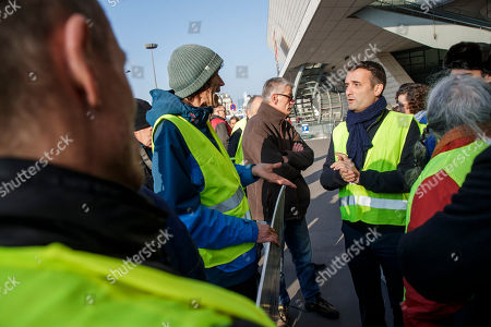 President of French political movement 'Les Patriotes' Florian Philippot (R) wearing a Yellow vest, as a symbol of French driver's and citizen's protest against higher fuel prices, speaks with a demonstrator (C-L) during a gathering as part of a nationwide protest to block roads and cause traffic chaos, in Paris, France, 17 November 2018. The so-called 'gilets jaunes' (yellow vests) protest movement, which has reportedly no political affiliation, is protesting over fuel prices.