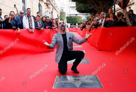 Luis Tosar (C) poses for photographers behind his star in the Almeria Walk of Fame shortly before being awarded Almeria Tierra de Cine Award as part of 27th Almeria International Film Festival, in Almeria, southern Spain, 17 November 2018. The festival runs from 17 to 24 November.