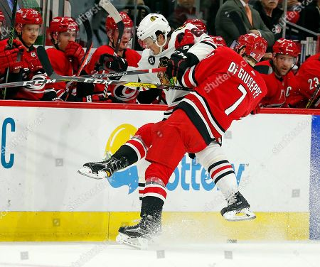 Phillip Di Giuseppe, Luke Johnson. Carolina Hurricanes' Phillip Di Giuseppe (7) collides with Chicago Blackhawks' Luke Johnson (62) during the second period of an NHL hockey game, in Raleigh, N.C