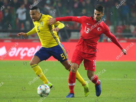 Sweden's Martin Olsson, left, and Turkey's Zeki Celik challenge for the ball during the UEFA Nations League soccer match between Turkey and Sweden in Konya, Turkey