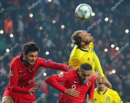 Sweden's Andreas Granqvist, Turkey's Okay Yokuslu, left, and Turkey's Cenk Tosun challenge for the ball during the UEFA Nations League soccer match between Turkey and Sweden in Konya, Turkey