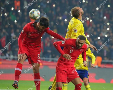 Sweden's Andreas Granqvist, atop right, Turkey's Okay Yokuslu, left, and Turkey's Cenk Tosun challenge for the ball during the UEFA Nations League soccer match between Turkey and Sweden in Konya, Turkey