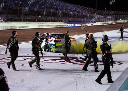 Under heavy security Tyler Reddick, driver of the (9) BurgerFi Chevrolet, starts to celebrate with a burnout after winning the NASCAR XFINITY Series Ford EcoBoost 300 Championship at the Homestead-Miami Speedway in Homestead, Fla