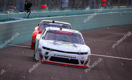 Tyler Reddick, driver of the (9) BurgerFi Chevrolet, races in front of Justin Allgaier, driver of the (7) BRANDT Professional Agriculture Chevrolet, during the NASCAR XFINITY Series Ford EcoBoost 300 Championship at the Homestead-Miami Speedway in Homestead, Fla