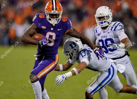 Clemson's Justyn Ross (8) avoids the tackle attempt by Duke's Jordan Hayes (13) and Brandon Feamster during the first half of an NCAA college football game, in Clemson, S.C