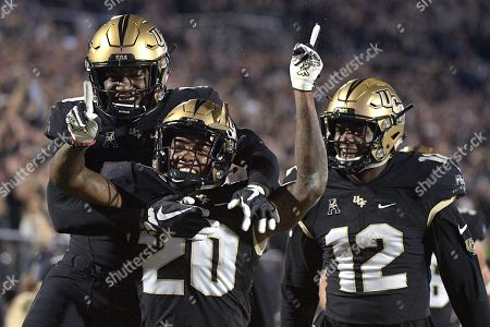 Central Florida defensive back Brandon Moore (20) is congratulated by linebacker Nate Evans, left, and linebacker Eric Mitchell after returning a blocked punt for 60 yards during the first half of an NCAA college football game against Cincinnati, in Orlando, Fla