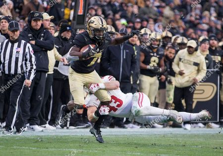 Stock Image of Purdue wide receiver Isaac Zico (7) runs with the ball after the catch as Wisconsin linebacker Ryan Connelly (43) pursues during NCAA football game action between the Wisconsin Badgers and the Purdue Boilermakers at Ross-Ade Stadium in West Lafayette, Indiana. Wisconsin defeated Purdue 47-44 in triple overtime