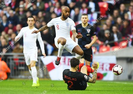 Croatia's Sime Vrsaljko (bottom) in action against England's Fabian Delph (C) during the UEFA Nations League soccer match between England and Croatia in London, Britain, 18 November 2018.