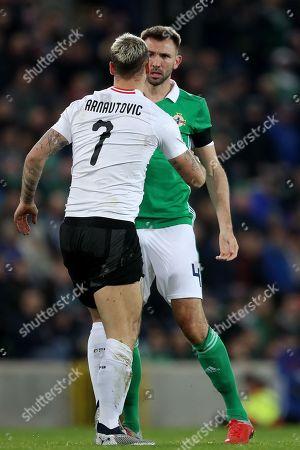 Marko Arnautovic of Austria squares up to Gareth McAuley of Northern Ireland
