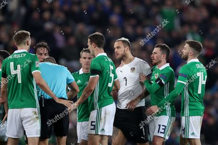 Corry Evans of Northern Ireland restrains Marko Arnautovic of Austria as he verbally clashes with Gareth McAuley