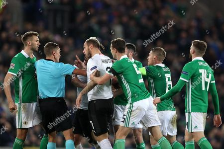 Marko Arnautovic of Austria points his finger at Gareth McAuley of Northern Ireland as tempers boil over