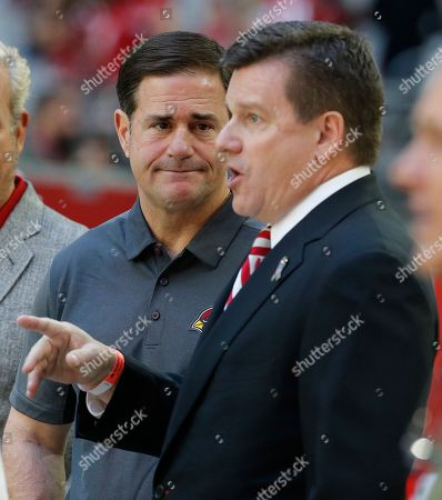 Arizona Cardinals president Michael Bidwill points as Arizona Gov. Doug Ducey watches prior to an NFL football game against the Oakland Raiders, in Glendale, Ariz