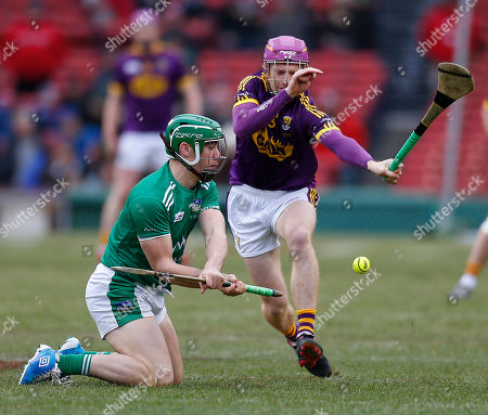 Limerick's Sean Finn (L) makes a pass from his knees as Wexford's David Dunn look to block in the semifinal game of the Fenway Hurling Classic held at Fenway Park in Boston, Massachusetts, USA 18 November 2018. The modified version of the amateur sport of Hurling to the Super 11s format is to allow the game to be played on smaller fields.