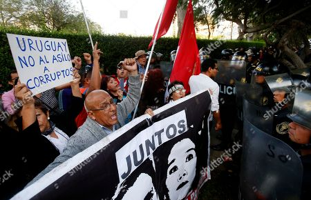"""People shout slogans against Peru's former President Alan Garcia outside the residence of Uruguay's ambassador to Peru, holding a sign showing an image of Garcia and Keiko Fujimori that says """"Together,"""" in Spanish, in Lima, Peru, . Garcia has sought asylum in Uruguay's diplomatic mission hours after a judge retained his passport as part of a corruption probe, Peru's foreign ministry announced Sunday"""