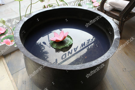 Silk water lilly floating in an 18th Century brass village cooking pot from the Punjab, £2200.