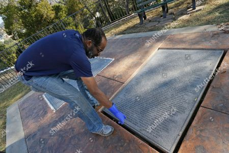 Jim Jones Jr. points to the names of family members on the Jonestown victim memorial in the Evergreen Cemetery in Oakland, Calif. Ceremonies were held at the cemetery to mark the mass murders and suicides 40 years earlier of more than 900 Americans orchestrated by the Rev. Jim Jones at a jungle settlement in Guyana, South America. The unclaimed or unidentified remains of more than 400 victims of the Jonestown tragedy on Nov. 18, 1978, are buried at the cemetery