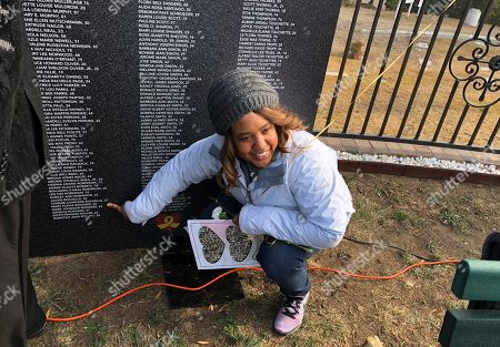 Erica Harden, of Sacramento, Calif., points out the names of six of her relatives who died in Jonestown, Guyana, on a portable memorial wall, which honors more than 300 children who were victims, as she attends a ceremony at Evergreen Cemetery in Oakland, Calif., . Ceremonies at the California cemetery marked the mass murders and suicides 40 years ago of 900 Americans orchestrated by the Rev. Jim Jones at Jonestown, a jungle settlement in the South American country